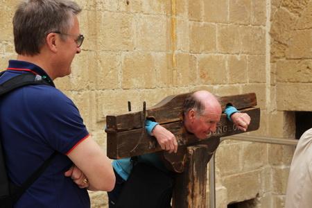 Очередной турист примеривает средневековые колодк